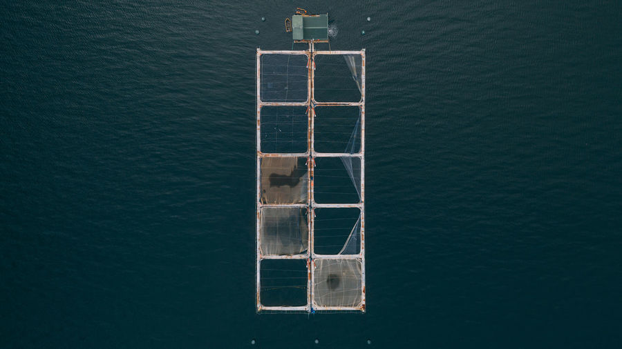 High angle view of salmon cages in the sea
