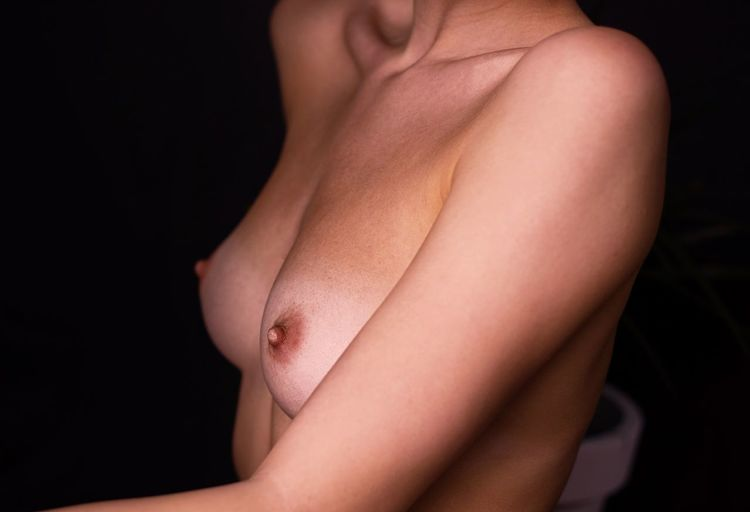 Midsection of shirtless woman against black background