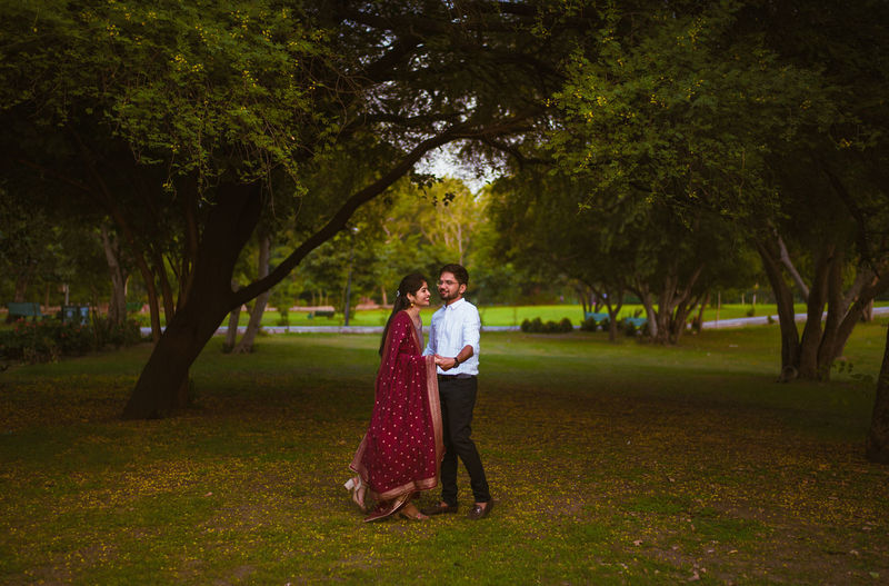 Full length portrait of a couple standing under trees in a park