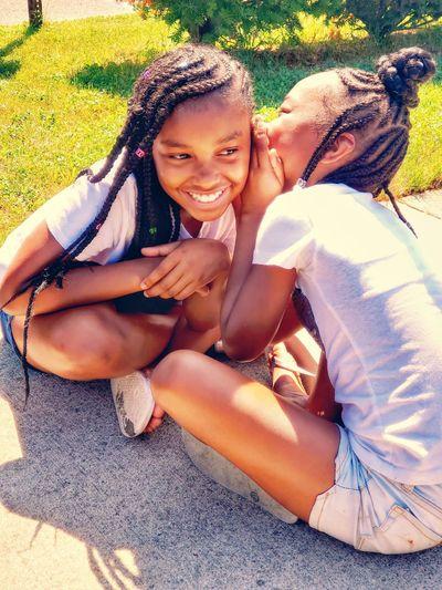 Girl whispering in friend ear