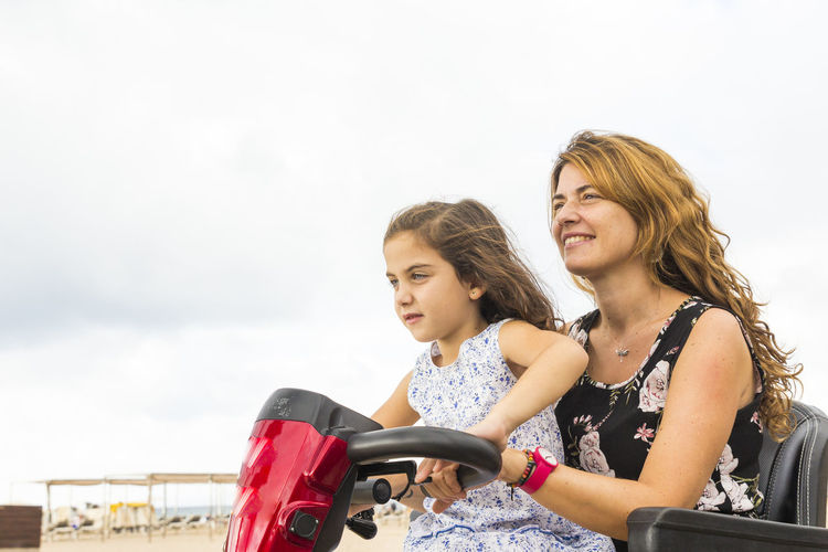 Mother and daughter riding vehicle against sky