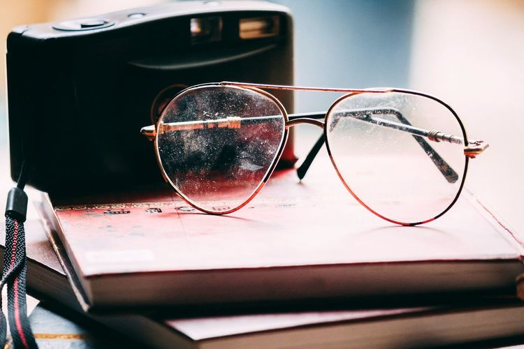 Close-up of eyeglasses and camera on diary