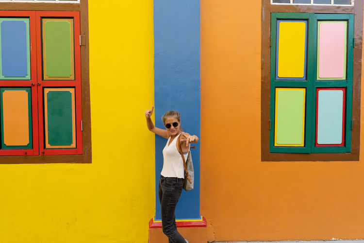 Full length of boy standing against yellow wall
