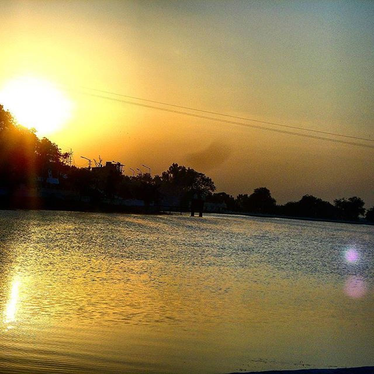 sunset, water, silhouette, nature, beauty in nature, reflection, scenics, tranquil scene, sun, sky, tranquility, outdoors, tree, vacations, no people, lake, day