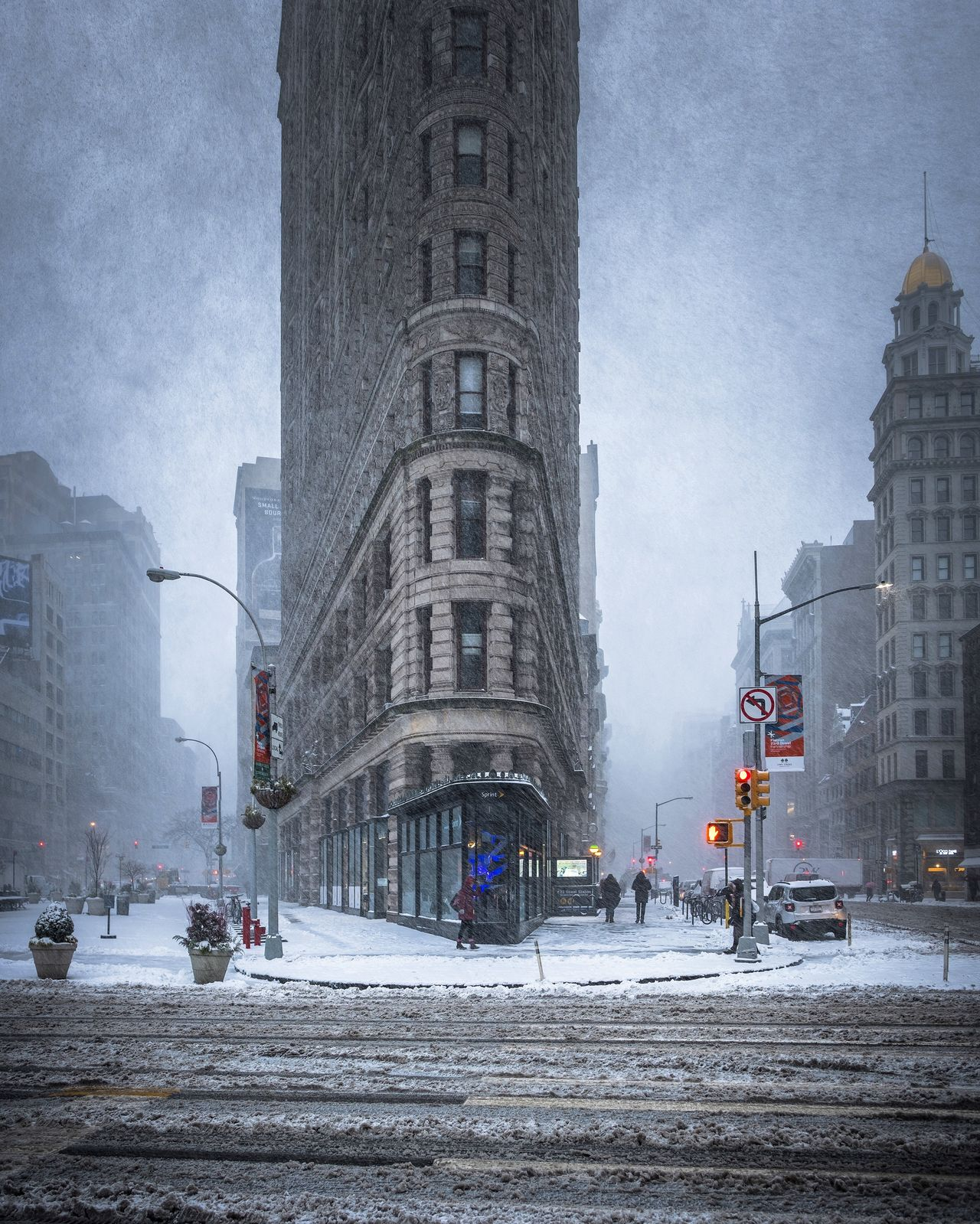 Flatiron building amidst streets in city during winter