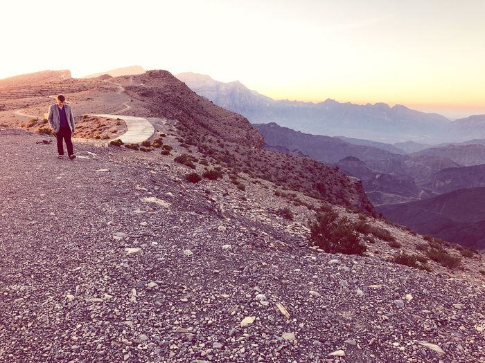 Top Of Mountain Travelling In Oman Tourist In Oman One Man Only Mountain One Person Hiking Adventure Exploration Landscape Full Length Arid Climate Nature Outdoors Adult Scenics Sunset Beauty In Nature Mountain Range Standing