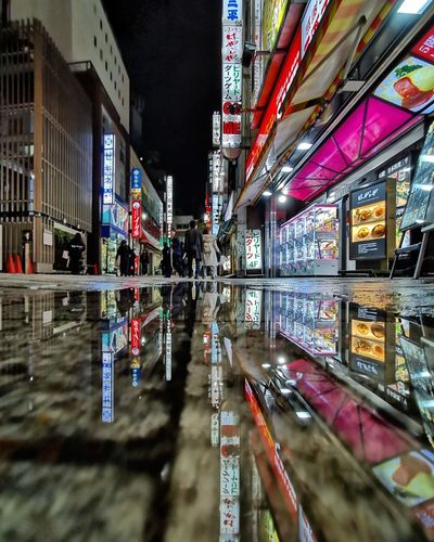 Reflection of illuminated building in puddle at night