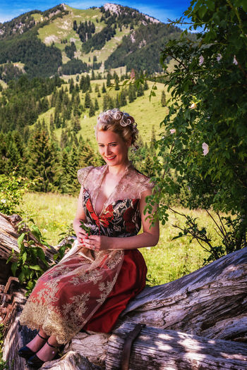 Portrait of romantic woman in dirndl with elaborate hairstyle holding flower in hand