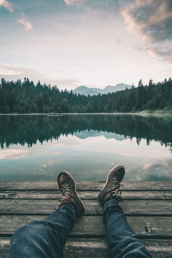 Relaxing at the mountain lake Chilling Crestasee First Person View Flims Graubünden Jetty Lake Legs Morning Morning Light Mountain Lake Mountains Peace Peaceful Pine Trees Reflection Relaxing Sitting Suisse  Sunrise Swiss Swiss Alps Switzerland Tranquility Trees Go Higher