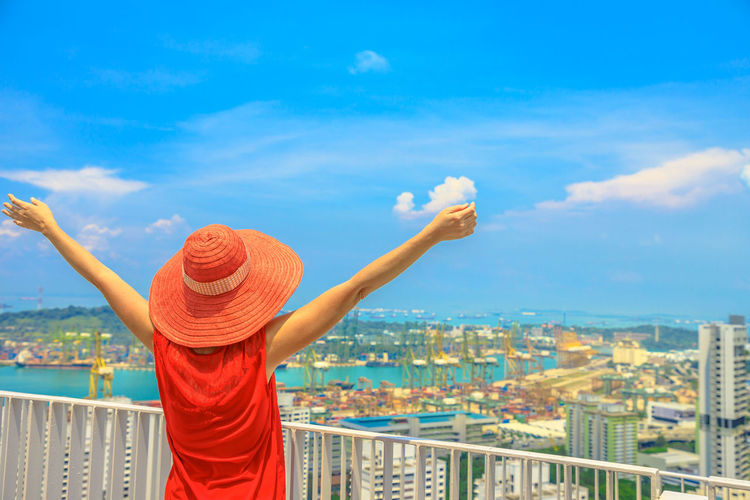 Carefree woman enjoys panorama from one of Singapore's tallest skyscrapers in Chinatown. Aerial view of Sentosa Island and Keppel Harbour. Lifestyle woman tourist looking Port with container terminal. Singapore Singapore City Woman Tourist Tourist Attraction  Tourist Destination People Girl Females Aerial View Skyline Cityscape Panorama Happy Travel Hat Lifestyle Enjoy Nature Tourism Sky Cloud - Sky Building Exterior Architecture One Person City Standing Built Structure Real People Rear View Human Arm Lifestyles Leisure Activity Day Limb Women Arms Raised Outdoors Human Limb