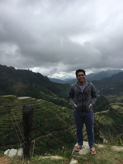 portrait of a young man Standing against the Scenic Banaue rice terraces . Cotton Slacks Slacks Gray Sky Terraced Landscape Terraced Field Terraced Field Portrait Young Man Standing Scenic Stairways To Heaven Terraced Fields Jackets Flipflops Travel Looking At Camera Agriculture