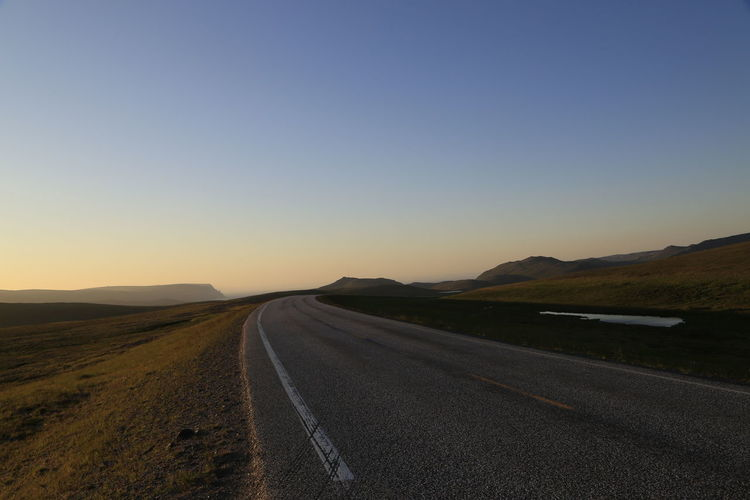 Road passing through landscape against clear sky during sunset