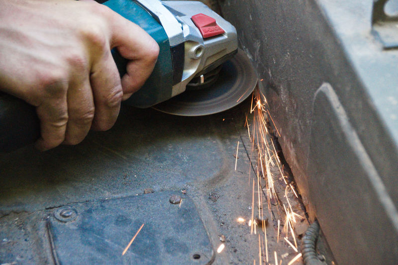 Close-up of hand cutting metal with angle grinder