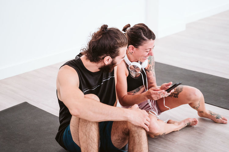 Woman using mobile phone while sitting by man on floor