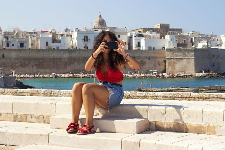 Woman Photographing While Sitting On Retaining Wall Sea