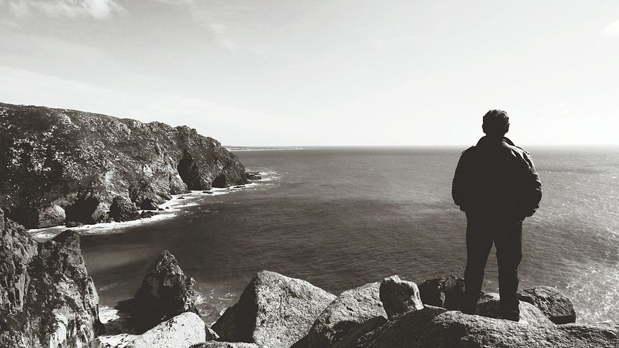Rear View Of Man Standing On Cliff In Front Of Sea
