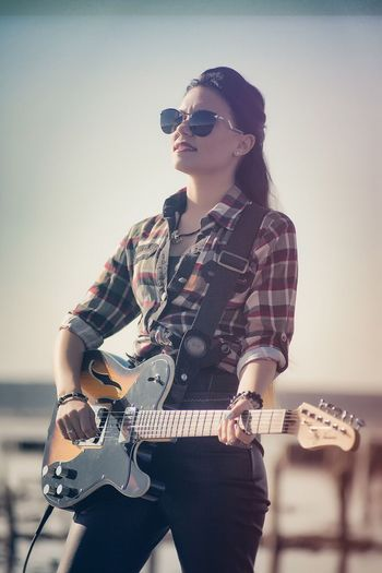 Young Woman Playing Electric Guitar Against Sky