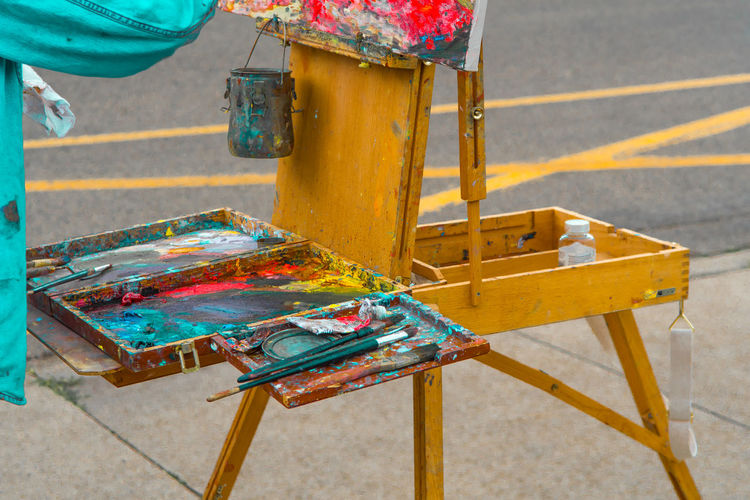 Paintbrushes And Pallete On Easel At Footpath