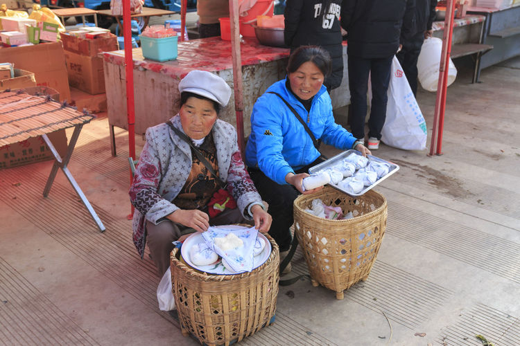 Shaxi, China - February 22, 2019: Chinese women selling local cheese in the Friday market in Shaxi old town Shaxi Yunnan Yunnan ,China Kunming, China Market Horse Horses South Silk Road