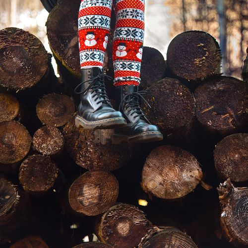 Low Section Of Woman Standing On Woodpile