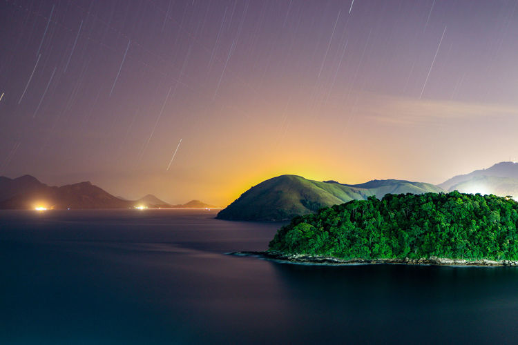 Long expossure at night in the sea Long Exposure Water Mountain Sea Tree Sky Landscape Calm Star Field Infinity Constellation Star - Space Space And Astronomy Shore Tranquil Scene Seascape Coast Island Horizon Over Water Galaxy Astronomy Coastline