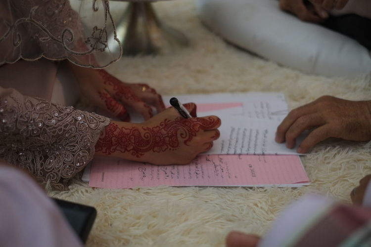 Cropped Henna Tattooed Hand Of Bride Signing Document On Rug