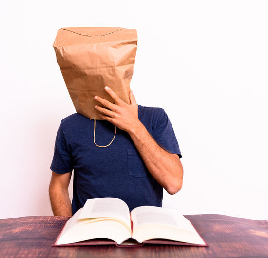Midsection of person holding book against white background
