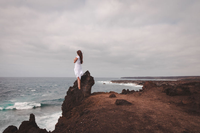 FEELING THE ELEMENTS. Lanzarote is an island in which the elements express at their maximum Earth Wind And Fire  Blowing In The Wind  Cloudy Ocean Side On Top Of The World The Great Outdoors - 2018 EyeEm Awards Beauty In Nature Blowing Cliff Cliffside Horizon Horizon Over Water Intimacy Land Long Hair Nature On The Edge One Person Outdoors Rock Sea Sky Standing Alone Volcanic Landscape Volcanic Rock Water The Traveler - 2018 EyeEm Awards