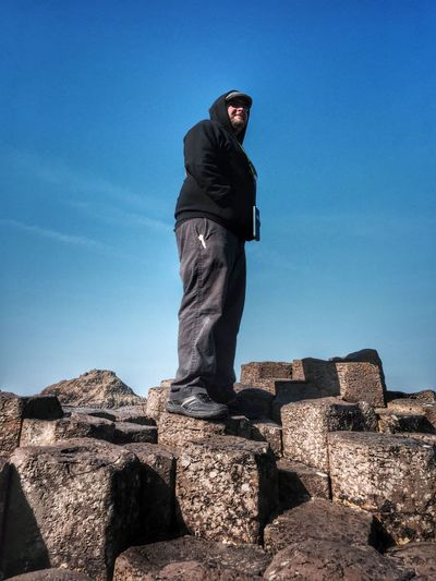 Low angle view of man standing on rocks at giants causeway against blue sky