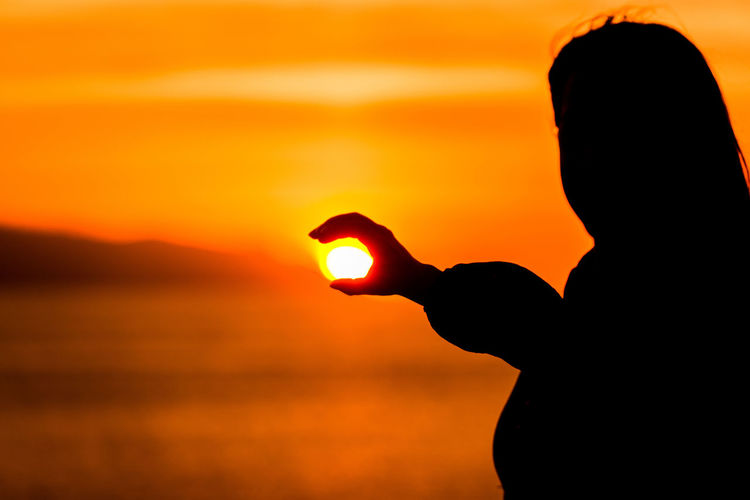 Optical illusion of silhouette woman holding sun at beach during sunset
