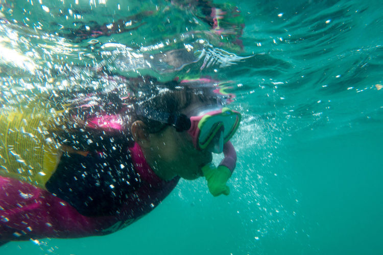 Kid snorkelling in sea with reflection, underwater shot