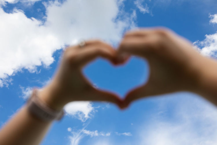 Low section of woman making heart shape against sky