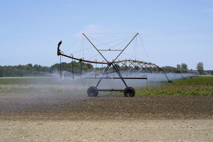 Watering Water Irrigation Equipment Irrigation System Irrigation Sky Field Land Day Nature Landscape Farm Transportation Rural Scene Mode Of Transportation Agriculture Environment Agricultural Machinery Land Vehicle No People Machinery Outdoors Plant Clear Sky Sunlight
