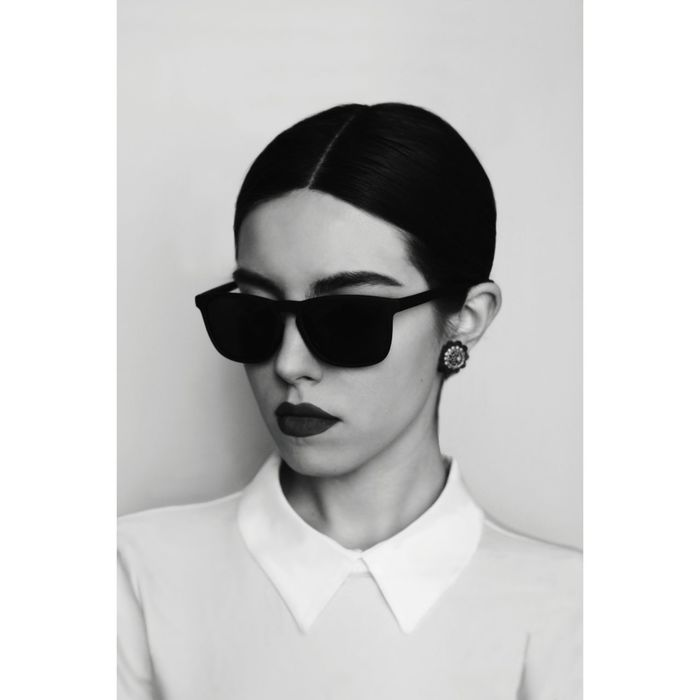 Close-up of young woman wearing sunglasses against white background