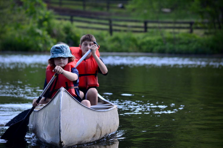 Brothers Canoeing On Lake