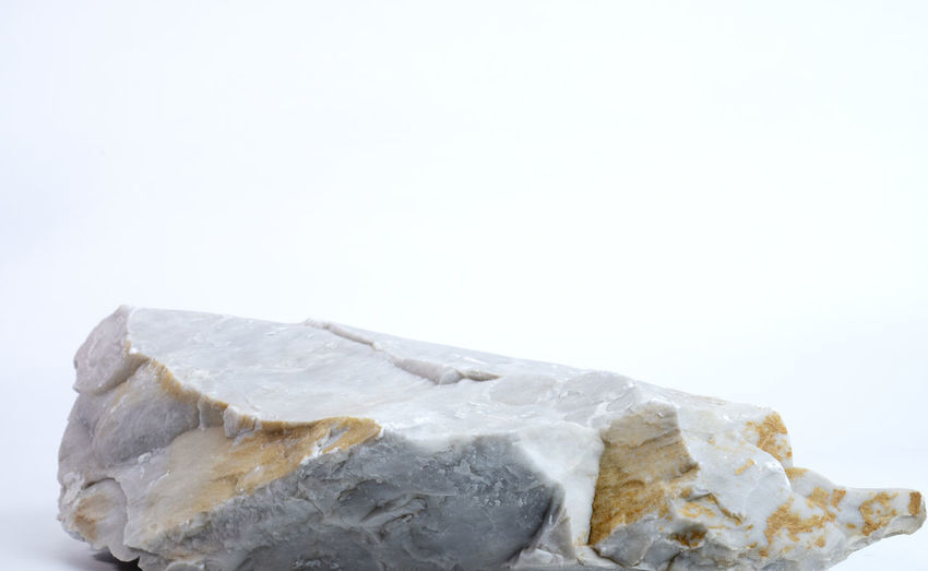 Close-up of ice cream on rock against white background