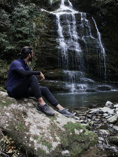 A young adult sitting on a rock right next to a waterfall.