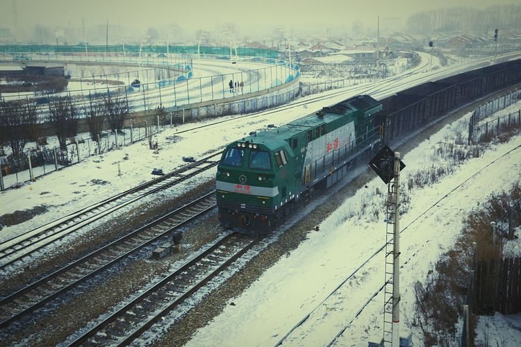 Train is coming in the snowy gloam. Train Gloam Snow Inner Mongolia Train Station Train Tracks Railway Overpass Flyover Fence Heavy Snow Winter Locomotive Train Engine