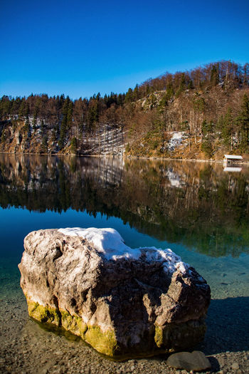 Rocks By Lake Against Clear Blue Sky