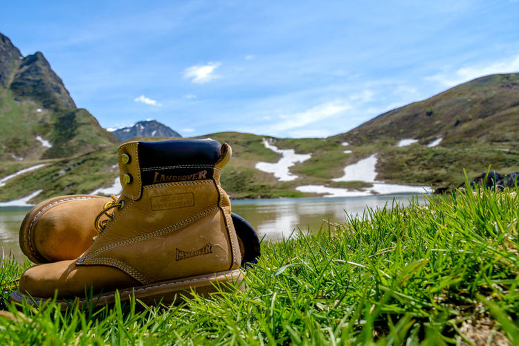 High angle view of shoes by lake against sky