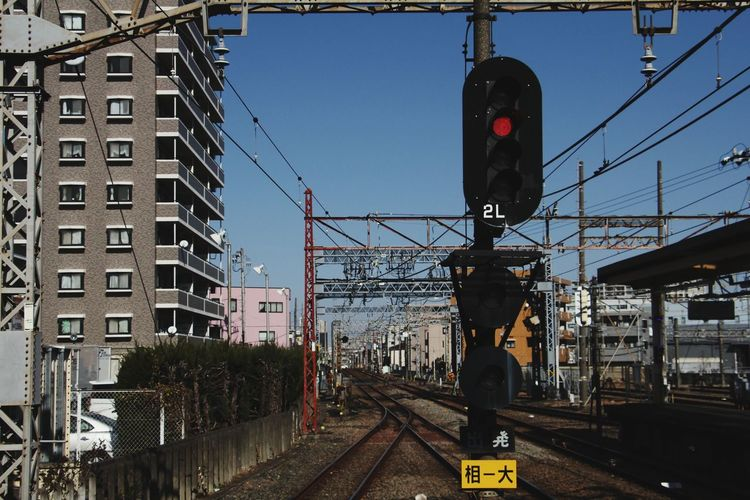 Train on railroad tracks in city against sky