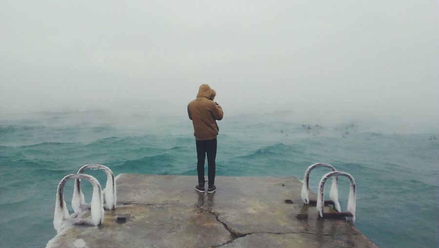 Rear View Full Length Of Man Standing On Pier By Sea During Foggy Weather