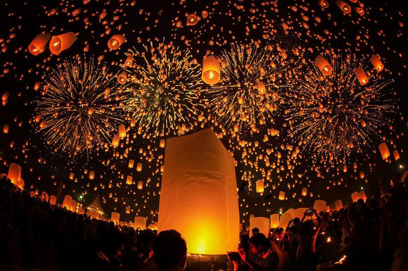 Illuminated Lanterns Over Crowd In City At Night During Yi Peng