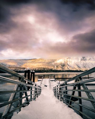 A vacant dock at Lake McDonald in Glacier National Park, Montana. Beauty In Nature Cloud - Sky Cold Temperature Day Lake Mountain Nature No People Outdoors Railing Scenics Sky Snow The Way Forward Tranquil Scene Tranquility Water Weather Winter