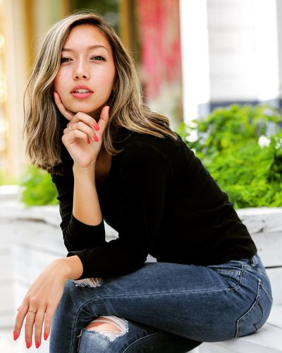 Portrait of a beautiful young woman sitting outdoors