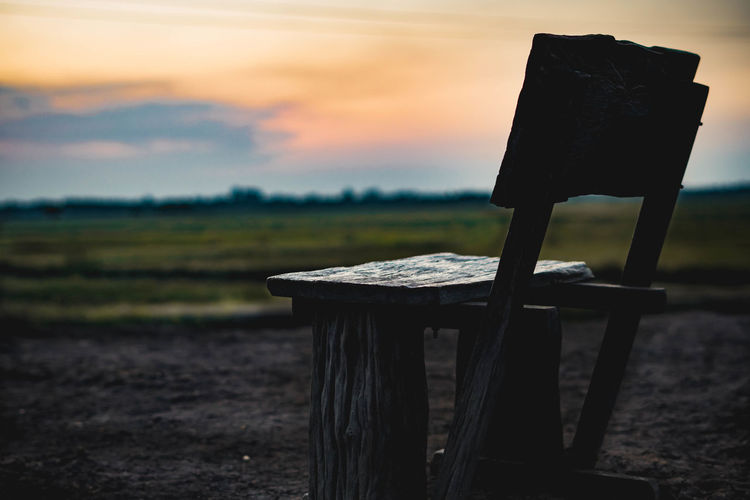 Empty wooden bench on land against sky during sunset