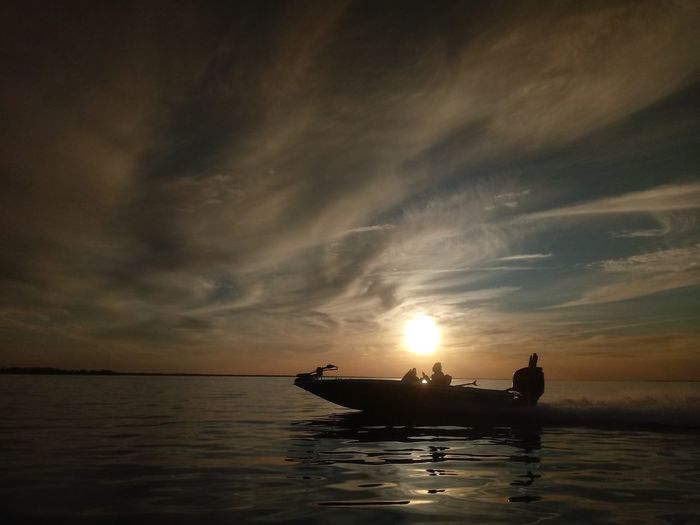 Silhouette boat in sea against sky during sunset
