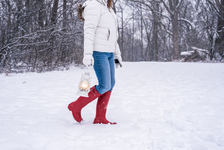 Full length of woman standing on snow covered field