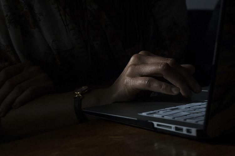 Close-up of hand using laptop in darkroom