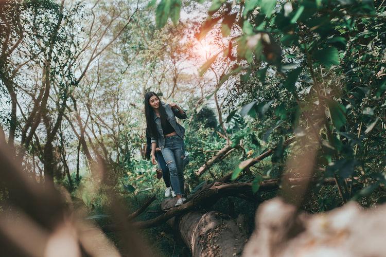 Full length of woman walking on fallen tree in forest